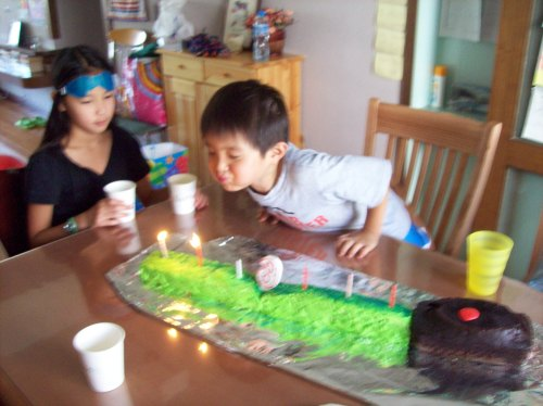 blowing out six candles on the light saber cake